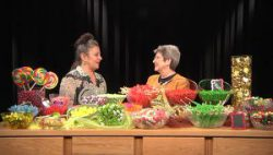 two women talking with a table full of candy in front